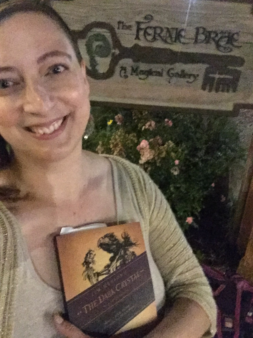 "I am smiling at the camera, holding a book, standing in front of a wooden sign that reads ""The Fernie Brae: A Magical Gallery"""